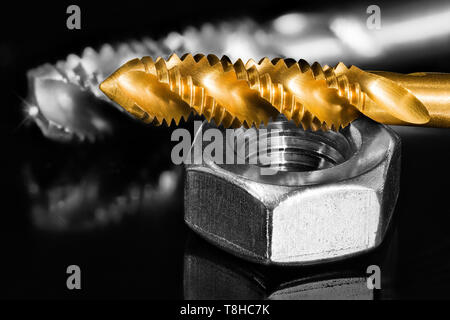 Stainless nut. Steel tap drill coated by titanium. Artistic detail. Spiral cutting tools for tapping. Reflection on black and white shiny background. - Stock Photo