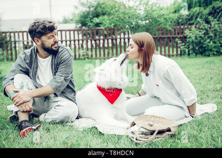 Dark-haired male looking at how his girlfriend kissing a dog - Stock Photo