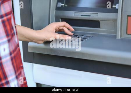 Woman entering pin code on cash machine, closeup - Stock Photo