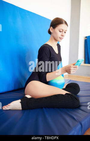 Teenage gymnast resting after training - Stock Photo
