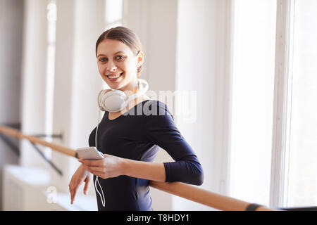 Cheerful ballerina leaning on barre - Stock Photo