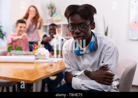 Teenager wearing glasses feeling offended by group mates - Stock Photo