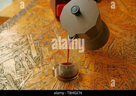 Pouring freshly brewed espresso coffee from Moka pot - Stock Photo