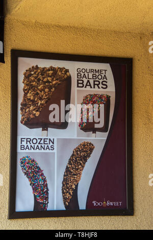 Balboa Island, California - October 12, 2018: Sign on a gold colored wall with a picture of types of ice cream pop bars and variations of frozen banan - Stock Photo