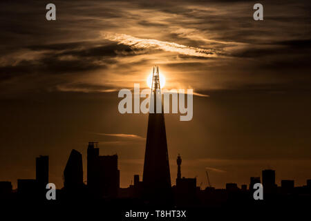 London, UK. 13th May, 2019. UK Weather: Dramatic evening sun is split behind The Shard skyscraper building. Credit: Guy Corbishley/Alamy Live News - Stock Photo