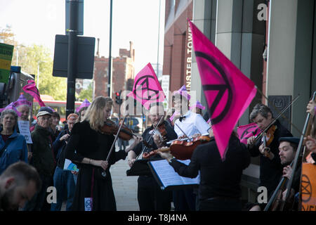 Extinction Rebellion activists target the International Maritime Organisation Climate Conference and delegates, May 13th 2019, Central London, United Kingdom. The activists handed out pink xr biscuits, a string ensemble played and a couple were busy re-arranging the deck chairs, all a play on the sinking Titanic. - Stock Photo