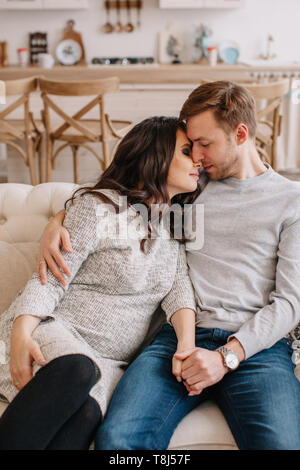 Happy couple sitting on a couch holding hands - Stock Photo