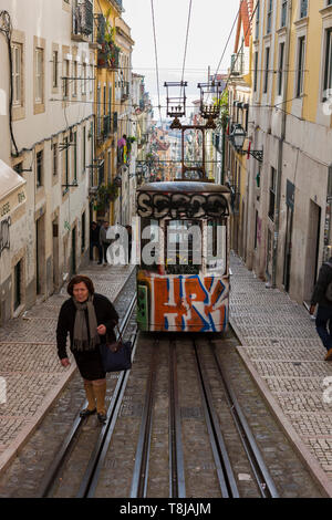 Lady walks on the tramlines in front of the Ascensor Da Bica, Lisbon's oldest funicular, Misericórdia, Lisbon, Portugal - Stock Photo