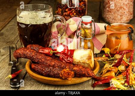 Dark beer in a glass and spicy sausages with chili peppers. Dried sausages on the table. - Stock Photo