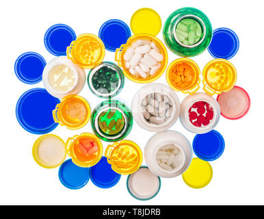 Horizontal shot looking down at a large group of various sizes and colors of pill bottles filled with pills.  Bottles and lids are on a light table. W - Stock Photo