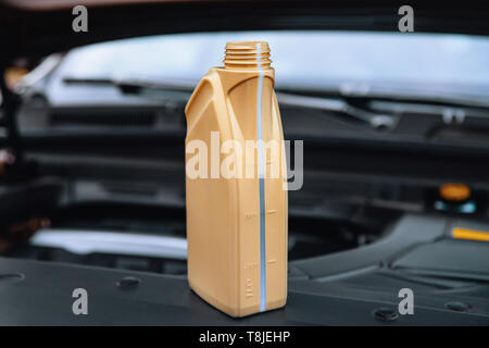 Capacity with engine oil near the car engine - Stock Photo