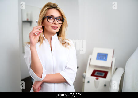 Portrait of young attractive beautician doctor with syringe in her hand. Cosmetologist holding medical tools. Practician in clinic or hospital. Nurse  - Stock Photo