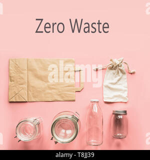 Set of jars and paper bag on pink background for zero waste storage and shopping. View from above.