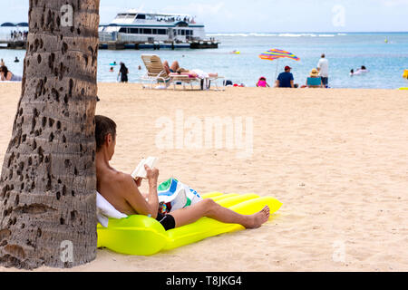 A man sitting on a yellow, flotation device, reading a book, while maintaining an appropriate social distance of at least six feet. - Stock Photo
