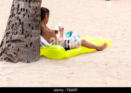 A man sitting off by himself reading a book on a yellow floatation device, Waikiki Beach, Hawaii, USA. - Stock Photo