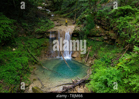 Woman in yellow jacket standing by a waterfall of a mountain river - stream flowing through thick green forest Beautiful natural pool, Pasjak Slovenia - Stock Photo