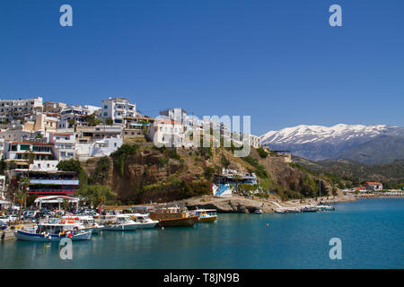 View on the charming fisherman's village Agia Galini on the South coast of Crete, in the background the snow-covered Idi Mountains - Stock Photo
