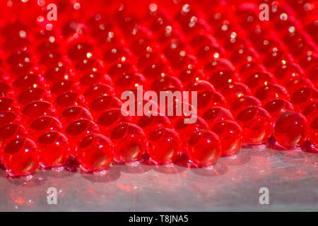 Water red gel balls with bokeh. Polymer gel. Silica gel. Balls of red hydrogel. Crystal liquid ball with reflection. Red balls texture background - Stock Photo