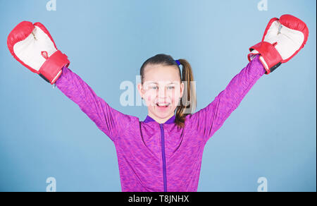 Female boxer. Sport upbringing. Boxing provide strict discipline. Girl cute boxer on blue background. Contrary to stereotype. Boxer child in boxing gloves. Confident teen. Enjoyment from sport. - Stock Photo
