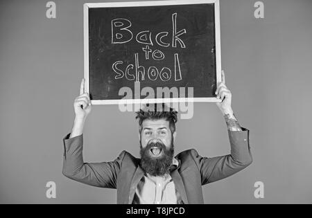 Teacher with tousled hair cheerful about school year beginning. Teacher bearded man holds blackboard with inscription back to school blue background. Keep working and be kind to people. Stay positive. - Stock Photo