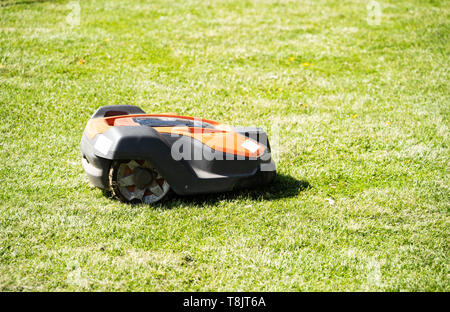 Husqvarna Automower robot lawnmower cutting a lawn, UK - Stock Photo