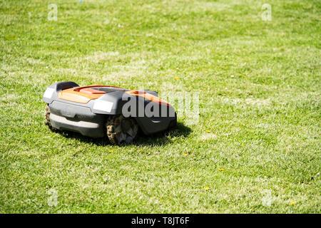 Husqvarna Automower robot lawnmower cutting a lawn, UK - Stock Photo