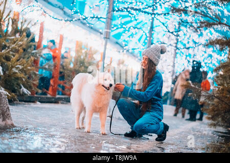 A young woman crouched beside a dog on a winter street. - Stock Photo