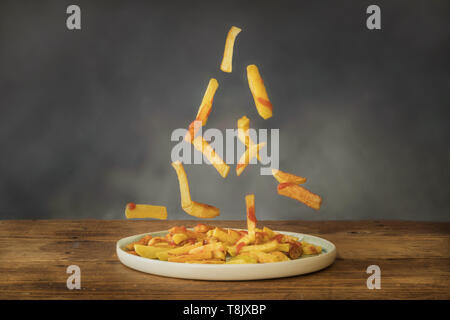 Fried potatoes with ketchup flying on a ceramic plate on an old wooden table - Stock Photo