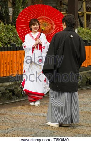 Young Japanese woman wearing traditional kimono holding umbrella looking at man also dressed traditional kimono, Gion Shirakawa, Motoyoshicho, Higashi - Stock Photo