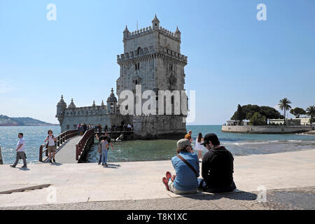 Rear back view of two young people sitting by the River Tagus Tejo riverside talking by Belem Tower historical building in Lisbon Europe KATHY DEWITT - Stock Photo