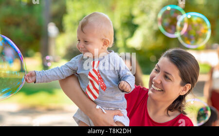 Cute baby and his mother catching soap bubbles in a summer day - Stock Photo