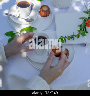 Enjoying coffee time in the garden. Served table with coffee, canele, flowers and book in the garden. Arrangement with a woman's hands. - Stock Photo