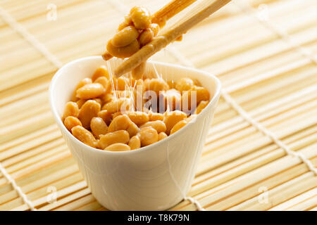 Eating healthy traditional japanese fermented soybeans called natto with chopsticks - Stock Photo