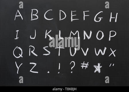 capital alphabet written in white chalk on a blackboard with some symbols - Stock Photo