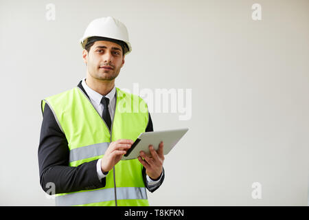 Pensive Engineer Holding Tablet - Stock Photo