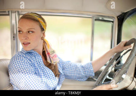 Young woman in 1950s outfit driving a vintage car - Stock Photo