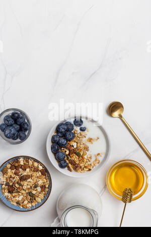 Close up granola with yogurt, blueberries, honey and nuts and spoon. Ingredients for healthy breakfast - Stock Photo