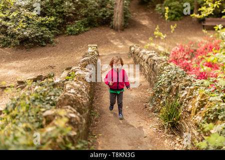 Colour portrait photograph of young girl exploring Branksome chine gardens at speed. Poole, Dorset, England. - Stock Photo