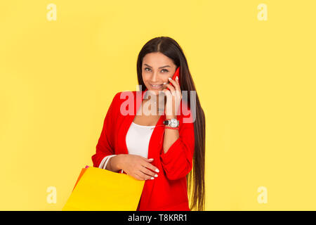 Beautiful young happy young woman with colorful shopping bag using smartphone looking at camera smiling, ordering something by cellphone. Multicultura - Stock Photo