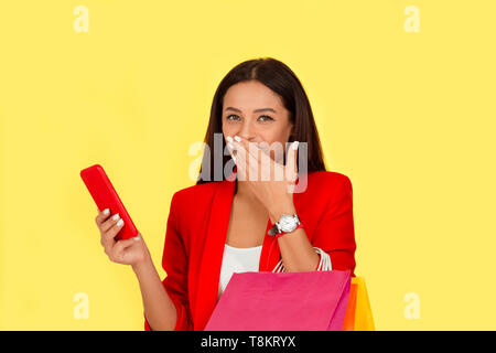 Portrait of a pretty excited woman with colorful shopping bags looking at mobile phone laughing happy fashion girl isolated on yellow background.  Mul - Stock Photo