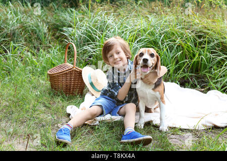 Cute little boy with dog resting in green park - Stock Photo