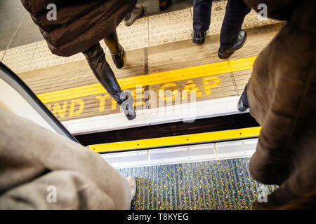 Directly above view at Mind the gap sign in London Underground metro train station with feets of pedestrians exiting entering metro train - Stock Photo