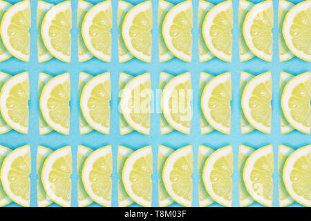 Bright lemon repeat pattern on a blue background. Flat lay summer concept. - Stock Photo