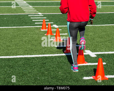 A high school female athlete performs running drills over orange cones on a green turf field on a bright sunny fall afternoon wearing gray spandex. - Stock Photo