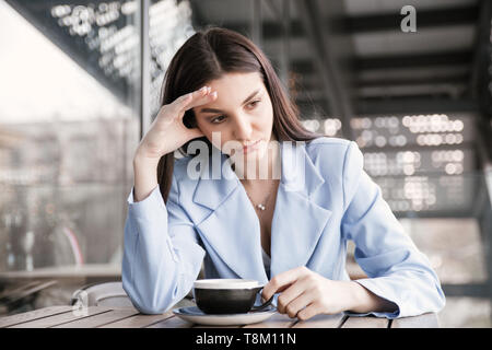 Depressed. Sad woman in a cafe holding head with hand. Closeup portrait of a beautiful hispanic girl wearing formal blue suit sitting at a table on a  - Stock Photo