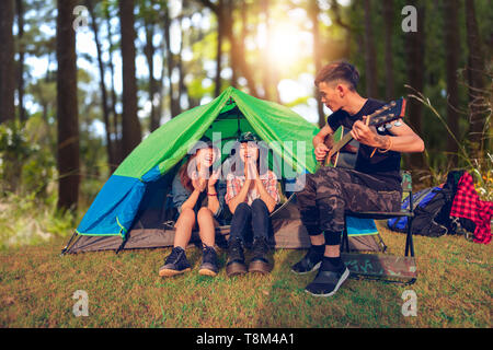 A group of Asian friends tourist drinking and playing guitar together with happiness in Summer while having camping - Stock Photo