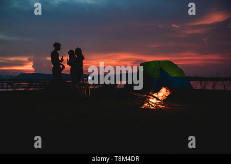 Silhouette  group of Asian friends tourist drinking and playing guitar together with happiness in Summer while having camping near lake - Stock Photo