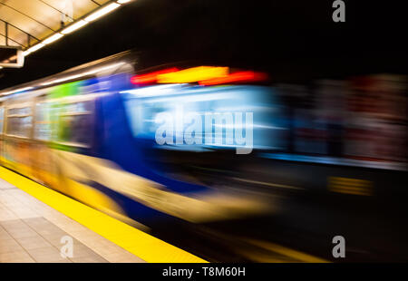 Colorful indoor abstract with motion blur of public transit subway train gaining speed exiting station platform. - Stock Photo