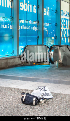 Homeless person's belongings and HIV sign at empty entrance to City Centre Skytrain Station in downtown Vancouver, BC. - Stock Photo