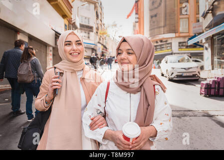 Beautiful Muslim women in headscarf and fashionable modern trendy clothes walk and chat together while having fun in Istanbul,Turkey.Modern Muslim wom - Stock Photo